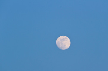 Full moon on clear blue winter sky