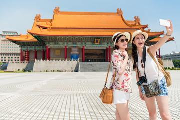 Girls take a photo with Chiang Kai-shek Memorial Hall.