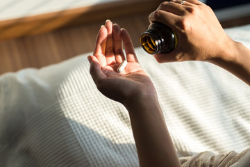 Woman hands with pills on spilling pills out of bottle,Female hand holding a medicine