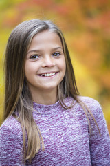 Beautiful Portrait of smiling little girl outdoors. Taking a cute picture on a warm fall day. Girl looking at the camera with a gorgeous grin