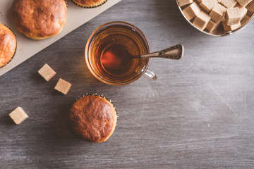 glass of tea and freshly baked muffins on the table - top view, copy space