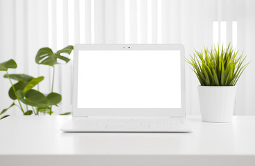 White laptop computer mockup with blank screen on office table