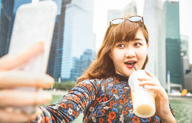 Pretty asian woman wanderer taking selfie at modern urban area of Marina Bay on Singapore skyline at sunset - Adventure travel lifestyle around south east Asia capital city - Bright warm vivid filter