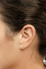 Oreille d'une femme en gros plan avec une boucle d'oreille