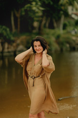 girl in a brown dress on the river bank on a background of palms