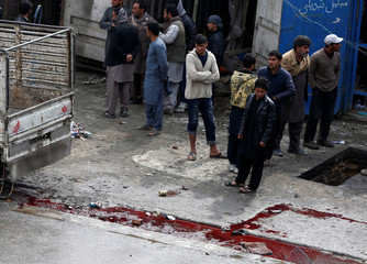 People gather near a bloodstain at the site of a suicide bomb attack in Kabul