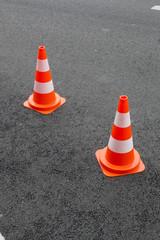 Deux cônes et signalisation sur du bitume neuf. Plots de trafic routier orange