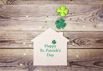 St.Patrick's day greeting message with lucky home symbol and four-leaf clover on wooden background.