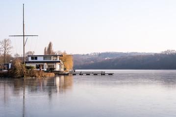 Haus am See mit Eisdecke im Winter