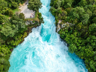 Stunning aerial wide angle drone view of Huka Falls waterfall in Wairakei near Lake Taupo in New Zealand. The waterfall is part of the Waikato River and is a major tourist attraction.