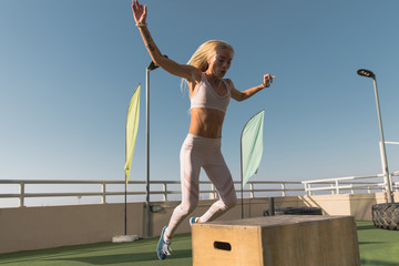 Fit young woman doing box jumping.