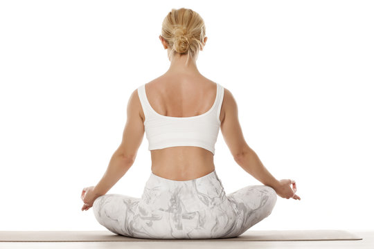 Yoga, sport, training and lifestyle concept - Young blonde woman doing yoga exercise. Portrait of young beautiful woman in white sportswear doing yoga practice. Lotus pose.