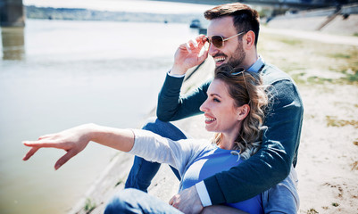 Dating. Romantic couple sitting on the riverside. Love and tenderness, romance. Lifestyle concept
