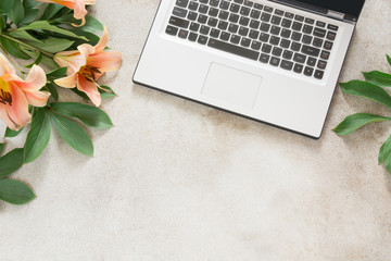 Female desktop with a laptop and flowers on vintage background.Top view composition with copy space.