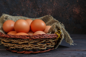 Rustic Easter background with quail and chicken eggs in straw nest on old wooden board with blank space for text