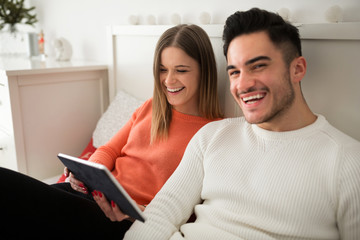 Happy couple sitting on bed using tablet