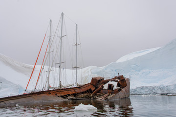 Two sailing yachts in the antarctic sea moored to rusty wreck