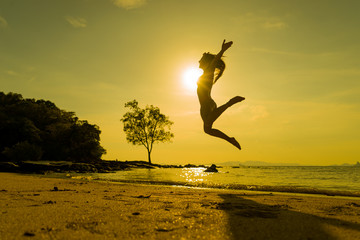 woman jumping on the tropical beach in Thailand