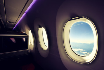 Stunning wide angle view of three airplane windows seen from a business class seat on a long haul widebody aircraft. Big TV screen on the left. Purple mood lighting on the ceiling. Bright day outside.