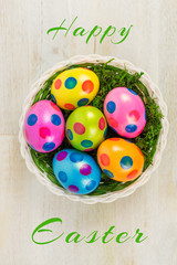 Easter basket with four colorful dotted Easter eggs and the words Happy Easter