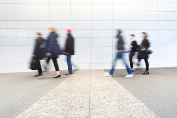 blurred commuters at a modern corridor