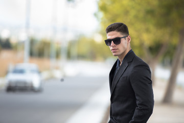 Good looking man in fashion shoot, wear black dress shirt and sunglasses standing on the edge of the street