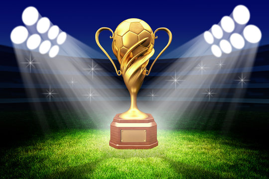Championship awarding ceremony, gold trophy award, football winner cup with a golden soccer ball in the light of spotlights on the green grass field of the stadium