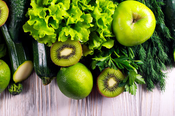 Green vegetables and fruits over wooden background