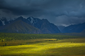 Beautifull  view to snow mountains and green field with sunlight and sky in the storm