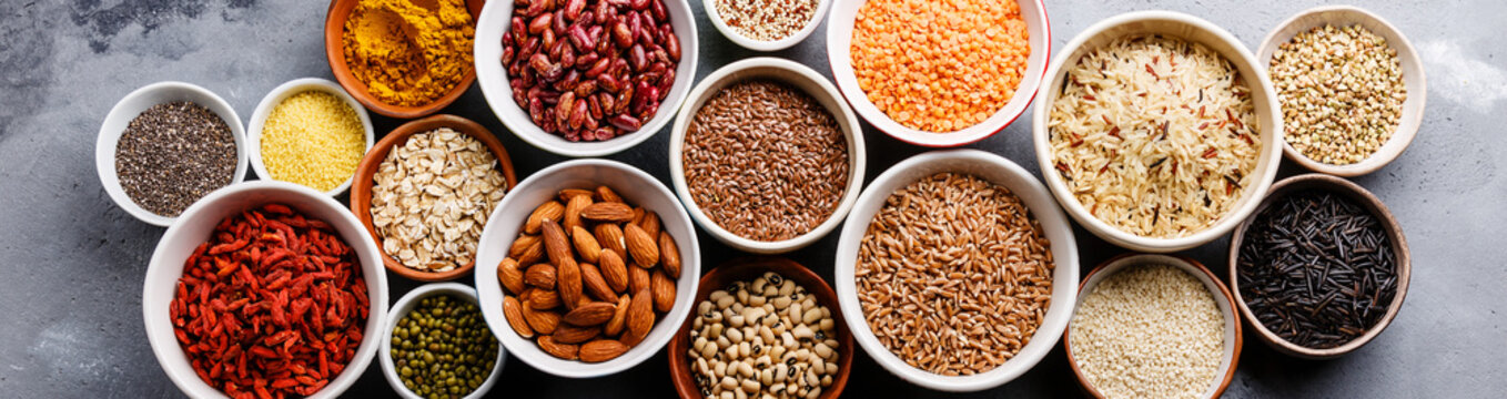 Superfoods and cereals selection in bowls: quinoa, chia, goji berry, mung bean, buckwheat, bean, turmeric, polba, bulgur, lentil, sesame, flax seed, wild rice, almond on grey concrete background