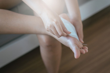 Woman using  white patch for relieve pain and relax on foot sole,Injury feet