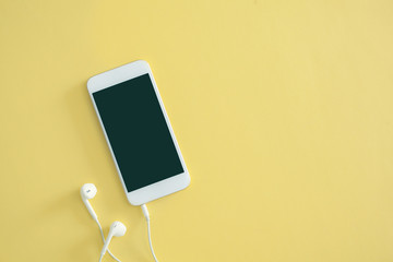 White mobile phone with earphone on yellow background