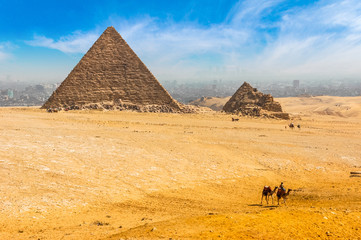 The Egyptian pyramids of Giza on the background of Cairo. Miracle of light. Architectural monument. The tombs of the pharaohs. Vacation holidays background wallpaper