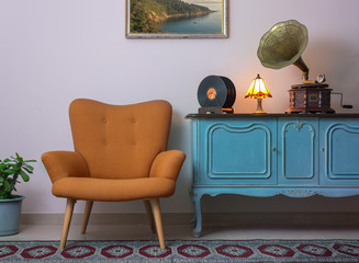 Vintage interior of retro orange armchair, vintage wooden light blue sideboard, old phonograph (gramophone), vinyl records and illuminated table lamp