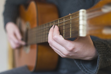 Woman hands playing acoustic guitar. Selective focus