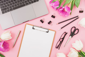 Laptop, clipboard, tulips flowers, glasses and accessories on pink background. Flat lay. Top view. Freelancer office concept