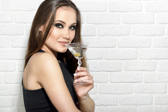 Young beautiful woman holding glass of martini with green olive and flirts in bar over white bricks wall