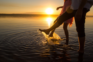 Young couples is walking in the water on summer beach. Sunset over the sea.Two silhouettes against the sun. Feet doing splashes of water. Romantic love story. Man and woman in holiday honeymoon trip.