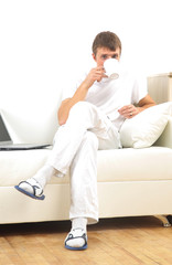 Handsome casual man sitting on couch having coffee at home.