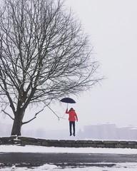 un ragazzo vola sotto la neve con ombrello