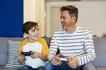 Happy father and son playing video game on couch at home