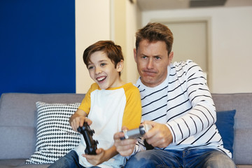 Father and son playing video game on couch at home