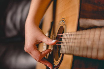 Female hand playing on acoustic guitar