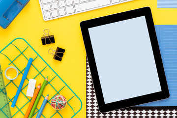 Yellow background with digital tablet and school supplies. Flat lay.