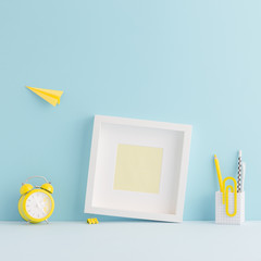 White blank photo frame and yellow supplies in creative young student workspace.