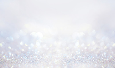 Glitter background in pastel delicate silver and white tones de-focused.