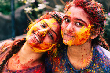 Smiling faces covered with holi colours looking at the camera.