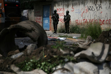 Armed forces members patrol the area close to a barricade during an operation against drug dealers in Jardim Catarina slum in Rio de Janeiro