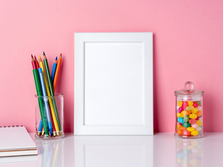 Blank white frame and crayon in jar, candys on a white table against the pink wall with copy space