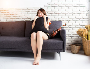 The young lady is sitting on sofa beside violin,at studio music room,with smile and happy face,prearpe for string class.vintage and art style.